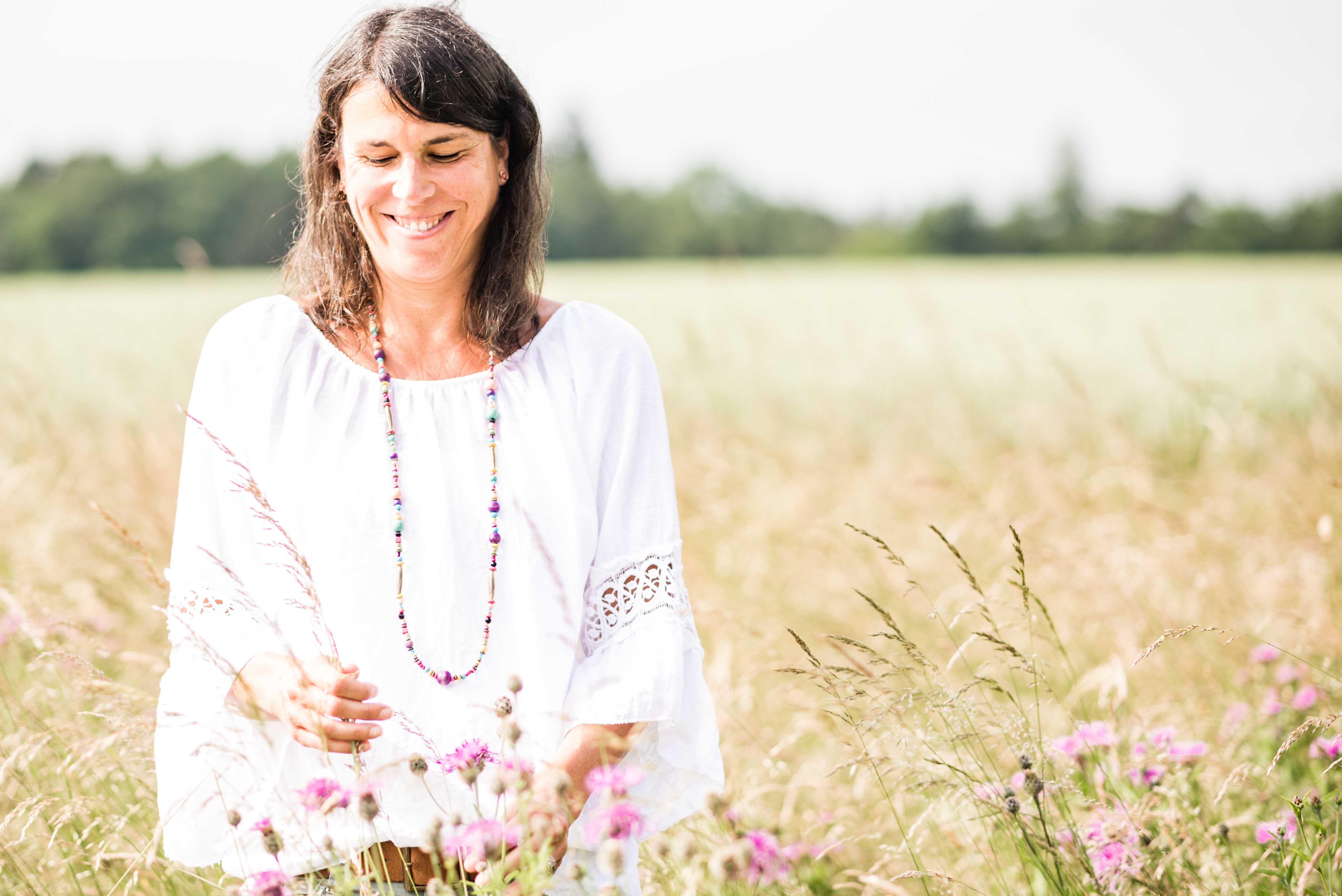 Barbara Baschnagel steht im Feld am linken Rand. Blick nach unten und Blumen in den Händen.