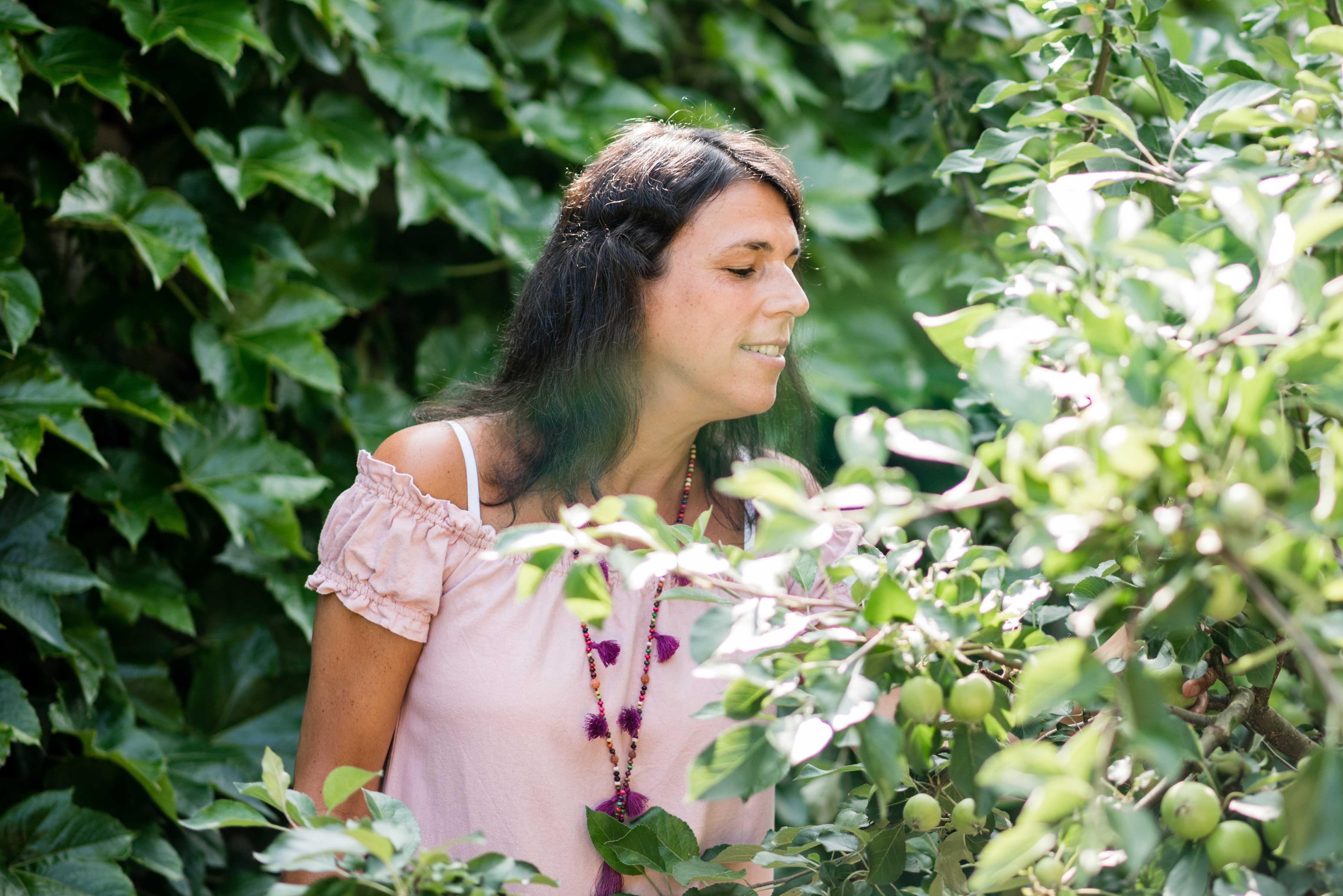 Barbara Baschnagel steht im Garten im Seitenprofil hinter einem Apfelbaum und riecht daran.