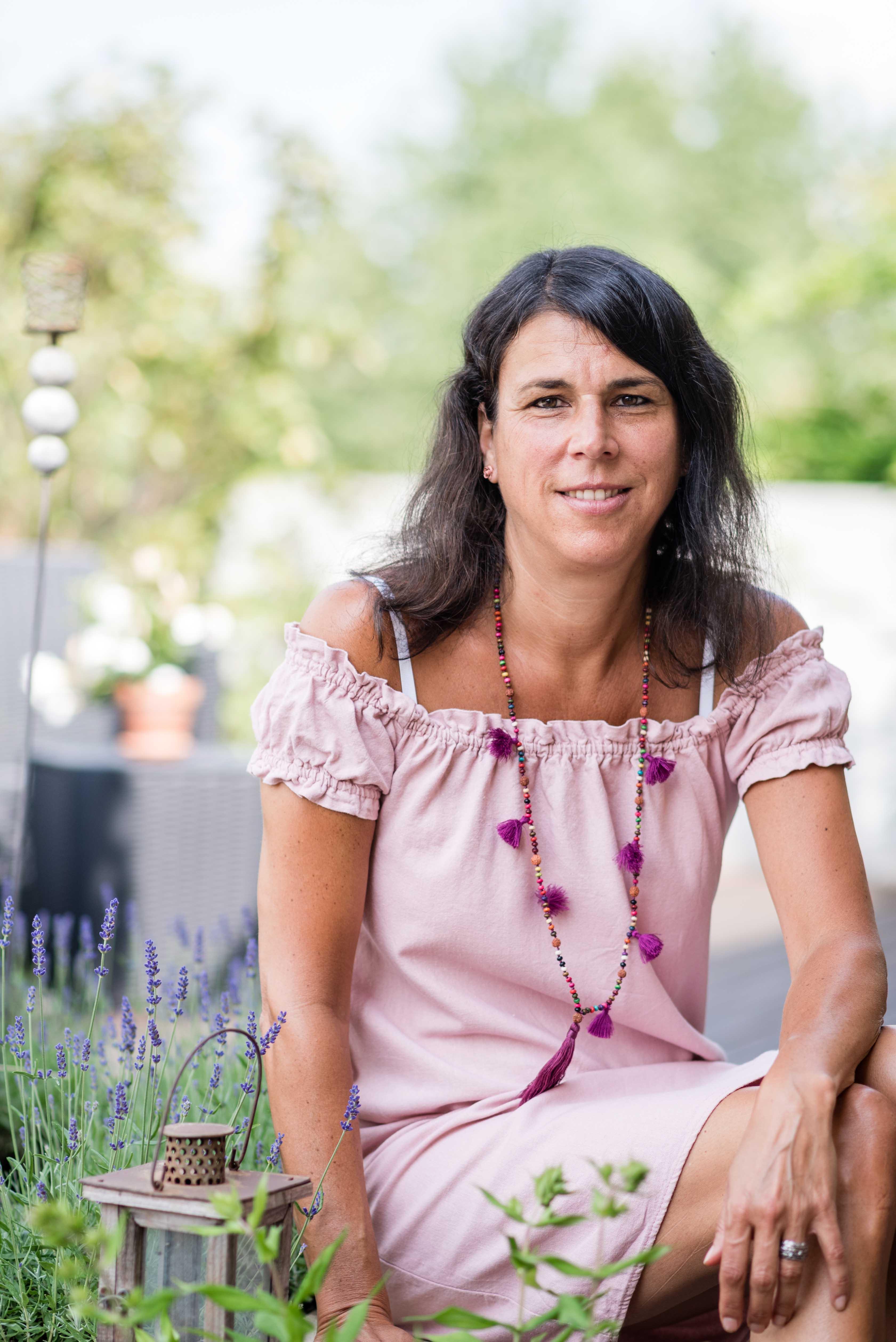 Barbara Baschnagel sitzt im Garten auf einer kleinen Mauer neben Lavendelblumen. Hochformatbild.