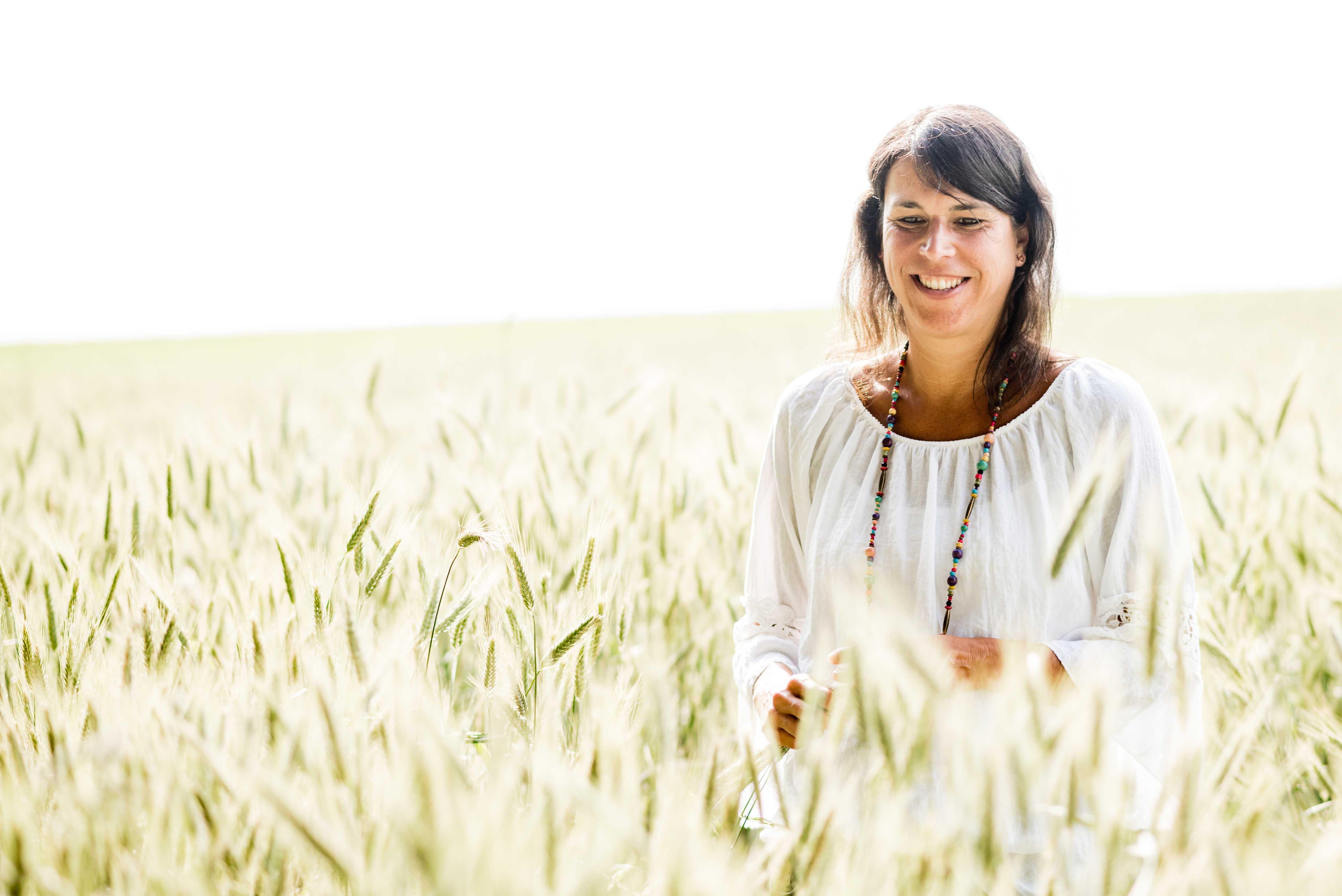 Barbara Baschnagel steht im Kornfeld und schaut mit nachdenklichem Blick leicht nach unten auf das Korn.
